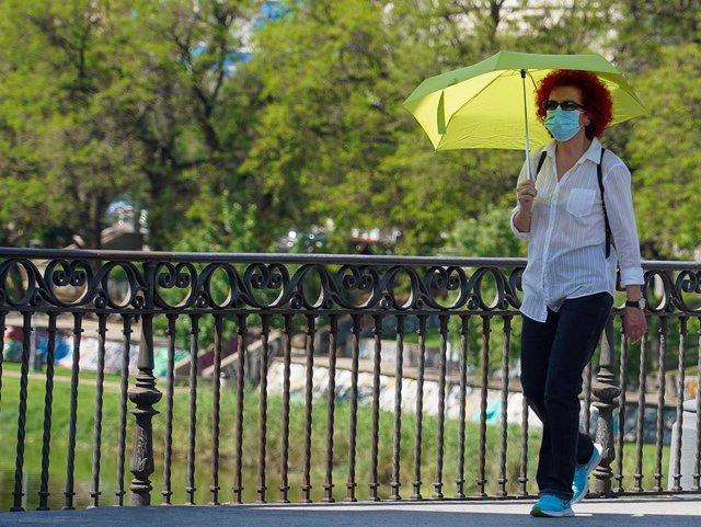Mujer pasea con un  paraguas amarillo.