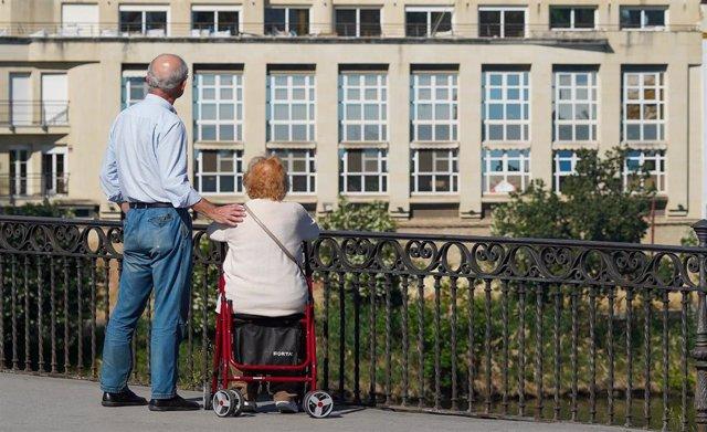 Personas mayor protegido con mascarilla pasea por el puente de Triana.
