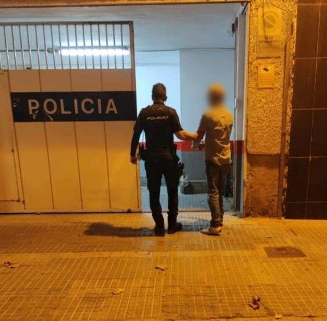 Un agente policial junto al detenido.