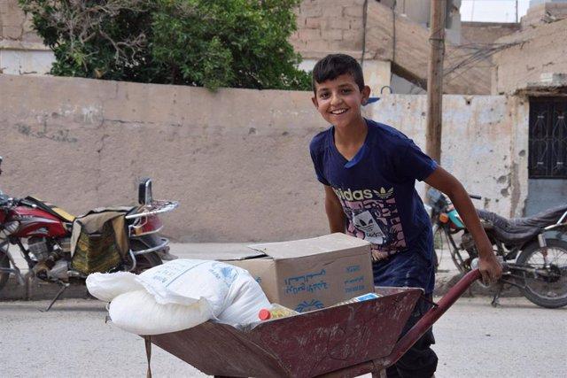 Un niño con ayuda alimentaria entregada por el PMA en Siria
