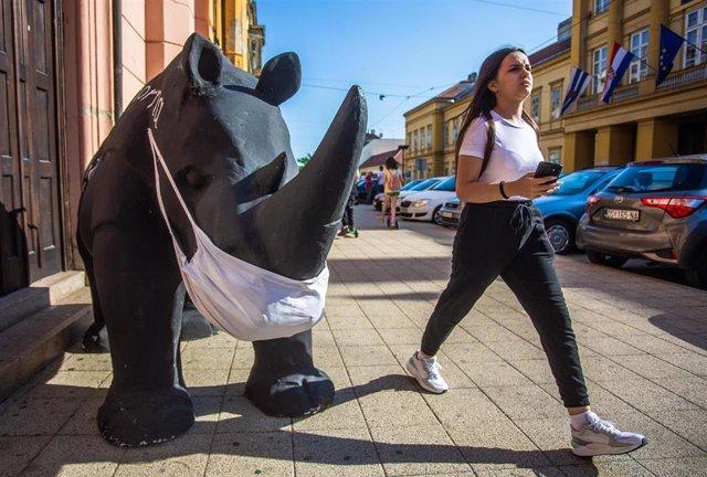 Estatua de un rinocerronte con mascarilla en Osijek, Croacia