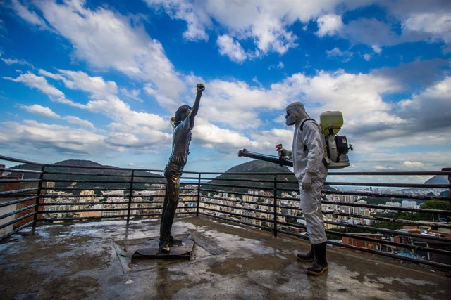 Un operario desinfecta una estatura de bronce situada en la favela de Santa Marta en Río de Janeiro.