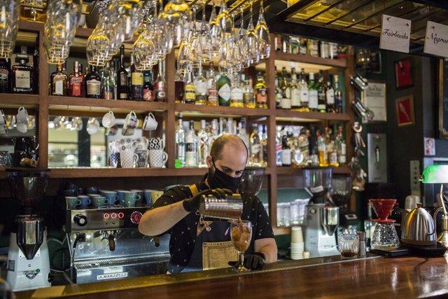 Un camarero prepara una bebida en un bar de Atenas, Grecia.