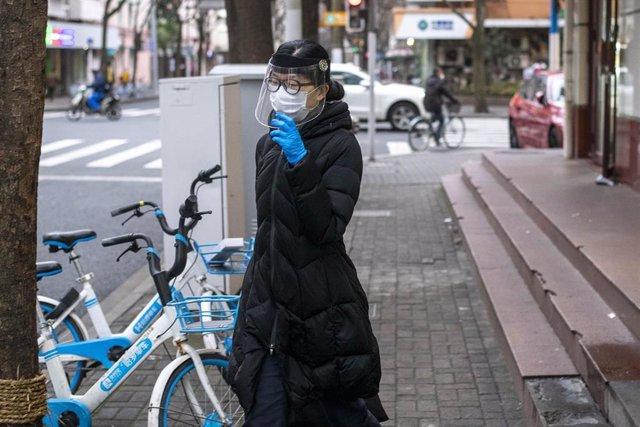 Una mujer camina por una de las calles de Shanghía ataviada con varias protecciones.