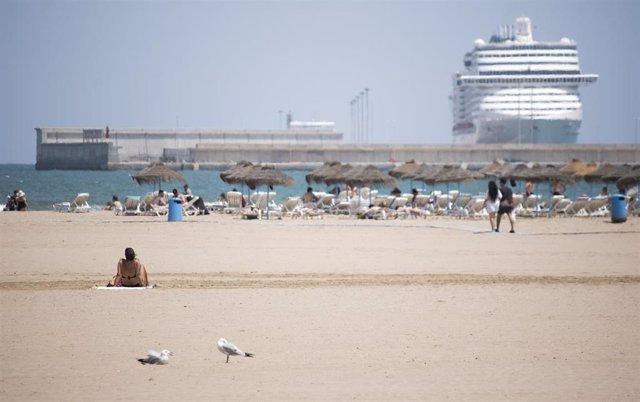 Una mujer descansa en la arena de la playa de la Malvarrosa de Valencia en un soleado día, víspera del inicio del estío