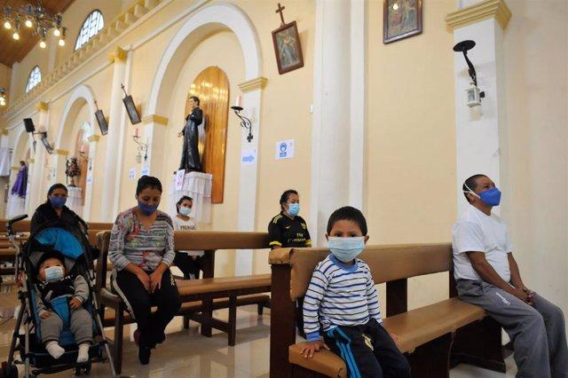 Personas manteniendo la distancia en una iglesia de Quito