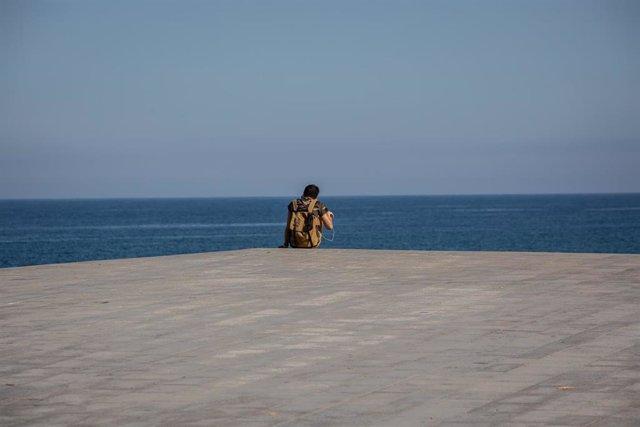 Un joven sentado en el Paseo Marítimo de la Playa de la Barceloneta durante el día 66 del estado de alarma decretado por el Gobierno a causa del Covid-19, en Barcelona/Catalunya (España) a 20 de mayo de 2020.