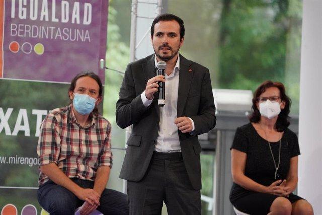 El coordinador general de IU y Ministro de Consumo, Alberto Garzón (c), durante su intervención junto al secretario general de Podemos y vicepresidente segundo del Gobierno y Ministro de Derechos Sociales y para la Agenda 2030, Pablo Iglesias