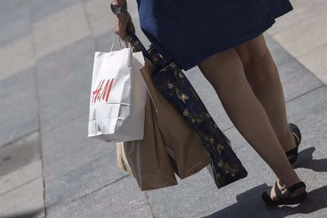 Una mujer pasea cargada con varias bolsas