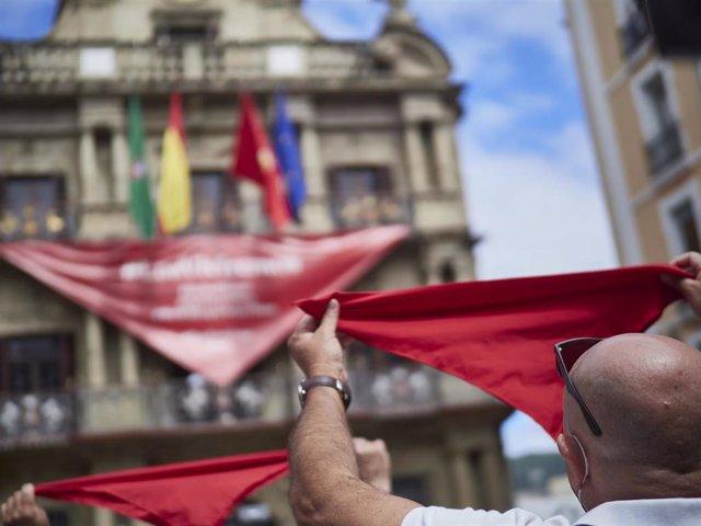 Un hombre alza un pañuelo rojo en las inmediaciones de la Plaza del Consistorio en el momento en el que de celebrarse los Sanfermines 2020 hubiera tenido lugar el famoso chupinazo, en Pamplona, Navarra (España), a 5 de julio de 2020. Pamplona afronta este