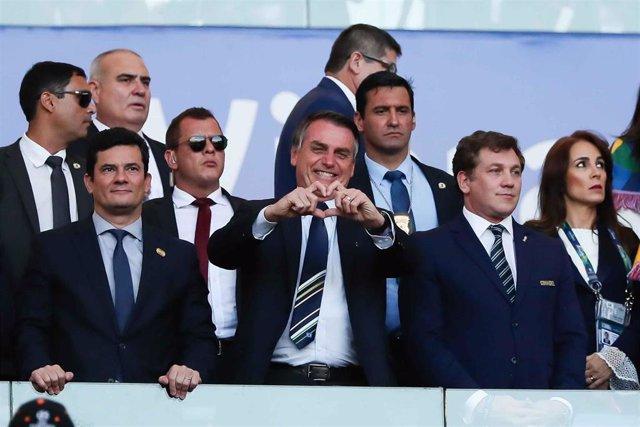 El presidente de Brasil, Jair Bolsonaro, y a su derecha, el que fuera ministro de Justicia, Sergio Moro, durante un partido de la slección de fútbol de Brasil en la pasada Copa América.