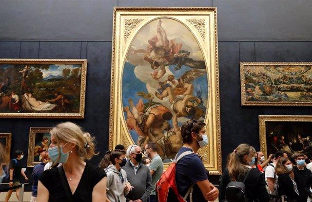 Visitantes con mascarilla en el Museo del Louvre, en París