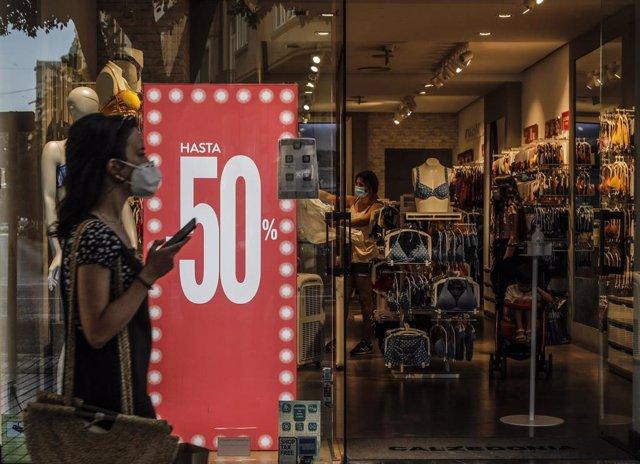 Una mujer protegida con mascarilla pasa al lado del escaparate de una tienda donde se observan carteles indicativos de rebajas en Valencia, Comunidad Valenciana (España) a 3 de julio de 2020. El 61% de los consumidores gastará 129 euros de media en las re