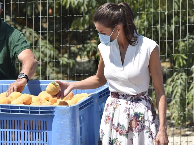 La Reina Letizia coge un melocotón durante su visita a la cooperativa de frutas La Carrichosa, en Cieza
