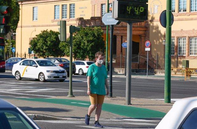 Un peatón paseando con mascarillas cuando el  termómetro marca 44º en la Avenida de la Palmera de Sevilla en un día en el que la ciudad está  en alerta amarilla por altas temperaturas. Sevilla a 22 de junio del 2020