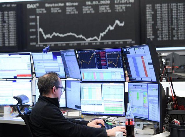 16 March 2020, Frankfurt/Main: A stock trader sits in front of his monitors in the trading room of the Frankfurt Stock Exchange. As a result of the worsening coronavirus crisis, the German share index Dax has fallen below the 9000 point mark. Photo: Arne