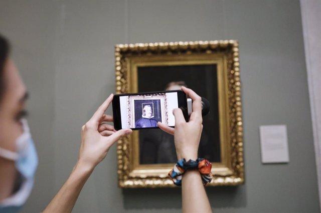 Una visitante saca una foto con el móvil a un cuadro del Museo Nacional del Prado, en el primer día en el que abre sus puertas. En Madrid (España) a 6 de junio de 2020.