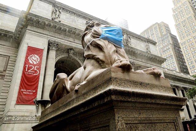 León con mascarilla frente a la Biblioteca Pública de Nueva York