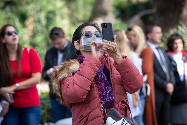 Una turista con mascarilla fotografía un monumento con su teléfono móvil.