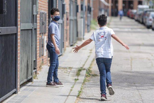 Dos hermanos pasean por la calle durante la pandemia, a 7 de mayo de 2020.