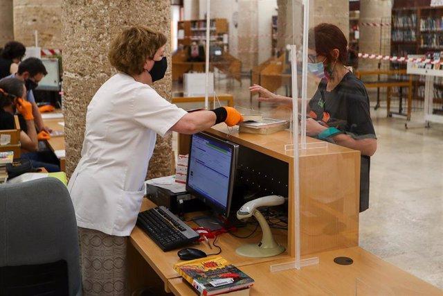 Una trabajadora, protegida y con una mampara, atiende a una usuaria de la biblioteca municipal de Valencia