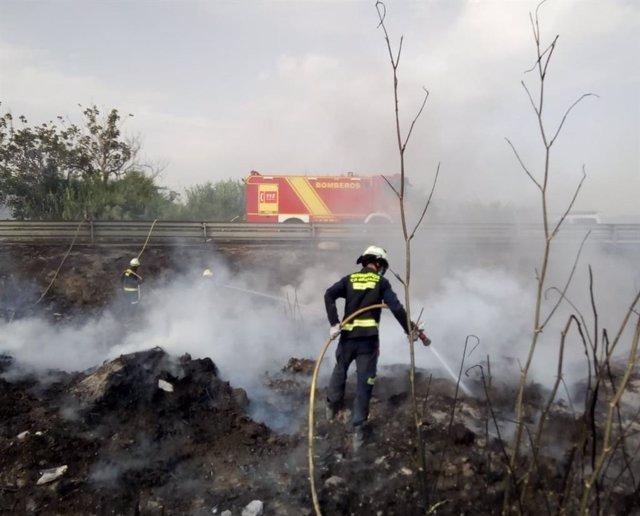 Los bomberos combaten el fuego en un cañaveral de Torrenueva Costa (Granada)