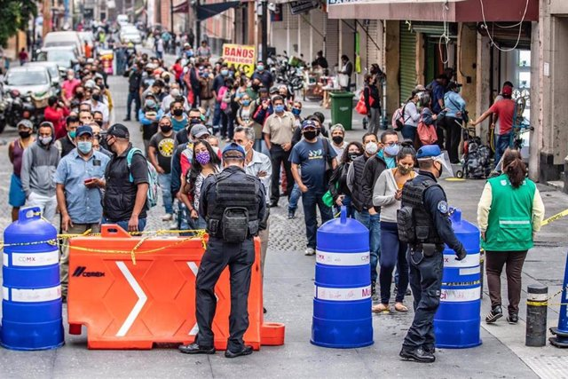 Decenas de personas gurdan la vez para poder acceder a las tiendas de un barrio de Ciudad de México, en medio de la desescalada de las medidas de confinamiento decretadas por la crisis sanitaria de la COVID-19.