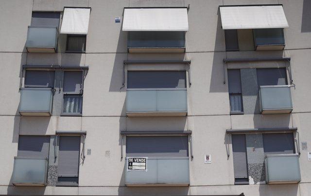 Cartel de 'se vende' en el balcón de un piso de un edificio de Madrid.