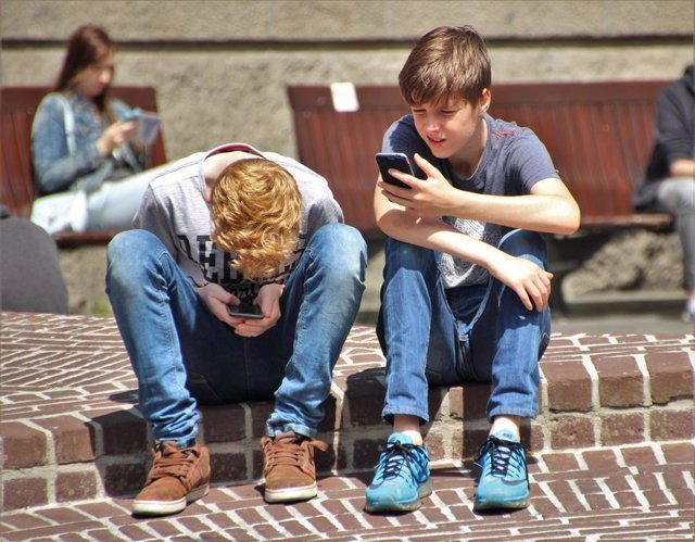 Imagen de recurso de dos adolescentes utilizando sus teléfonos móviles