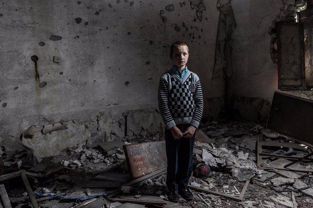 Un niño en una escuela destruida por el conflicto en el este de Ucrania