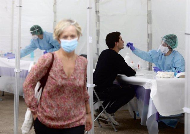 Una sanitaria le realiza un frotis nasal a un vecino de Ordizia en una de las carpas instaladas en el parque Barrena por el Ayuntamiento de Ordizia para realizar test ante el posible brote de COVID-19 detectado en la localidad guipuzcoana, en Ordizia, Gui