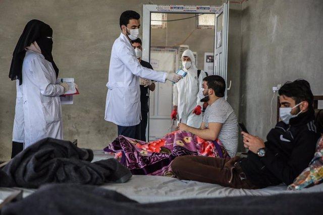 Un médico toma la temperatura de dos refugiados sirios que permanecen en cuarentena dentro de unas instalaciones habilitadas cerca de la frontera con Turquía.