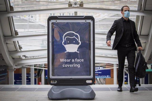 Cartel que promueve el uso de mascarilla en una estación de Edbimburgo