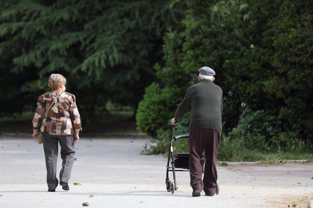 Una mujer y un hombre de edad avanzada pasen por la calle.