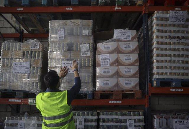 Personal del banco de alimentos etiqueta los alimentos entregados por la Agrupación de Apoyo Logístico n.º 21 (AALOG 21) de Torreblanca (Sevilla) y donados por Supermercados Día al Banco de Alimentos de Sevilla (Andalucía, España), a 14 de abril de 2020.