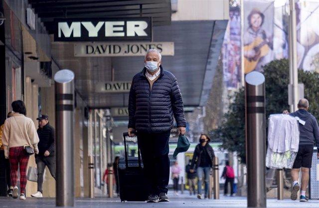 Un hombre con mascarilla en una calle de Melbourne