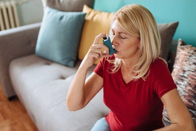 Persona con asma, inhalador.