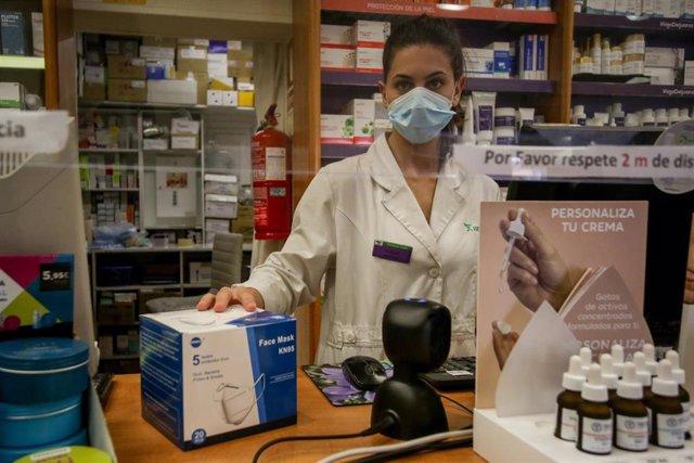Una farmacéutica de la farmacia Iñigo de Juana trabaja en el mostrador el mismo día en el que comienzan las entregas de mascarillas modelo KN95 que desde hoy y hasta el próximo 2 de julio podrán recogerse de manera gratuita en las farmacias de la Comunida