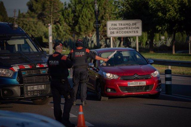 Un Mosso d'Esquadra controla el acceso a la A2 dirección Barcelona en Lleida, capital de la comarca del Segrià, en Lleida, confinada por un brote de Covid-19