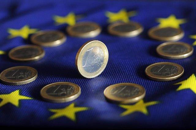 Monedas de euro sobre una bandera de la UE