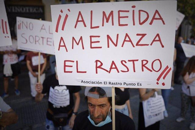 """Un hombre lleva un cartel en el que se lee '¡¡Almeida amenaza El Rastro!!', durante la concentración para denunciar que El Rastro está """"amenazado"""" bajo el lema 'Por la reapertura ya del Rastro de Madrid respetando a todos y cada uno de los titulares de lo"""