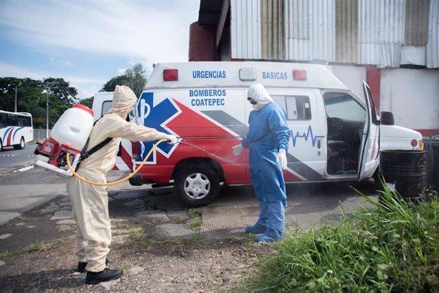 Dos trabajadores sanitarios desinfectándose por el coronavirus en México.