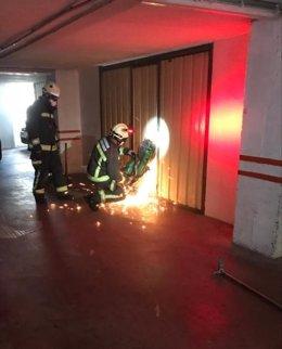 Bomberos abren la puerta del garaje donde se ha encontrado al hombre fallecido