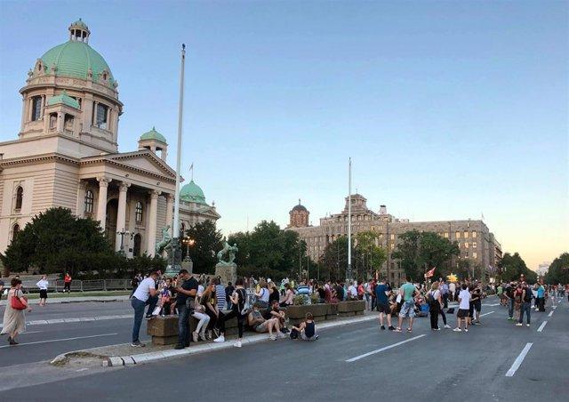 Imagen de varios manifestantes frente al Parlamento de Serbia.