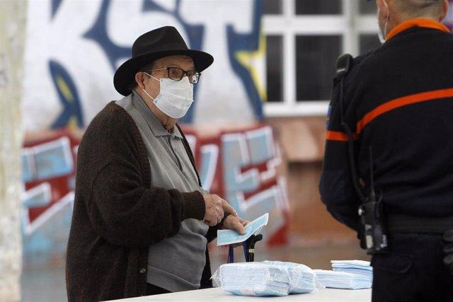 Transeúntes recogen mascarillas puestas a disposición de viajeros y usuarios de transporte público en las inmediaciones de la estación Intermoda, en Palma de Mallorca, Islas Baleares, (España), a 14 de abril de 2020.