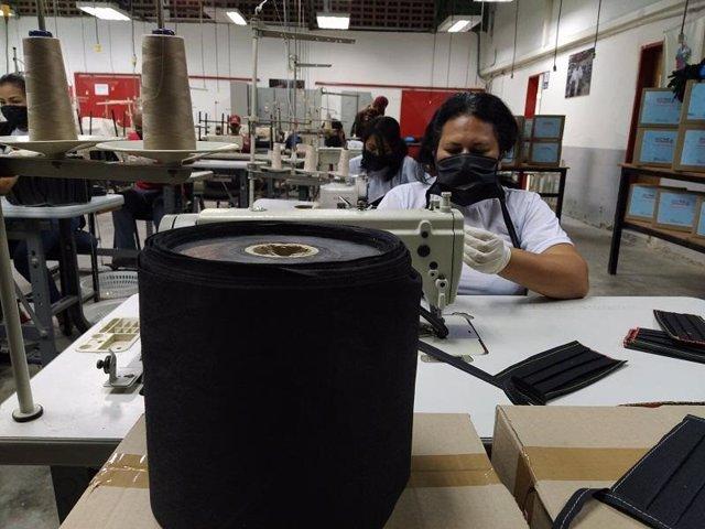 Trabajadora con mascarilla en un taller textil en Venezuela