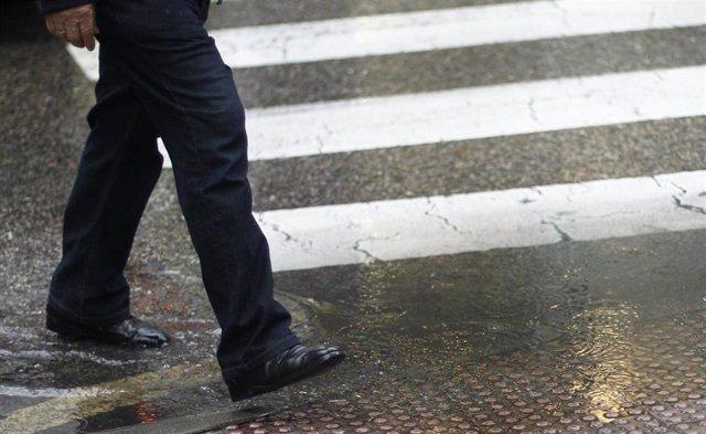 Un hombre mayor pisa un charco formado por las lluvias que han caído en Madrid al cruzar un paso de peatones.