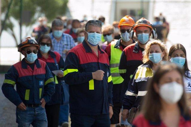 Trabajadores de Alcoa ataviados con el uniforme de la fábrica acuden a votar en las elecciones autonómicas de Galicia en el Pabellón Os Castros, en Burela