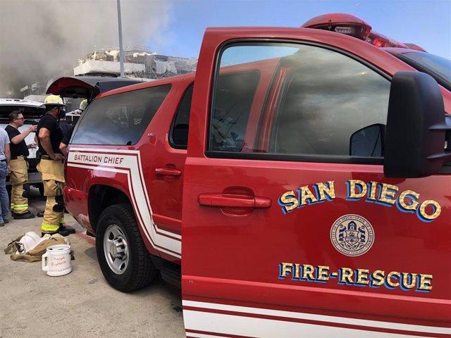 Bomberos durante un incendio en un buque de guerra en San Diego