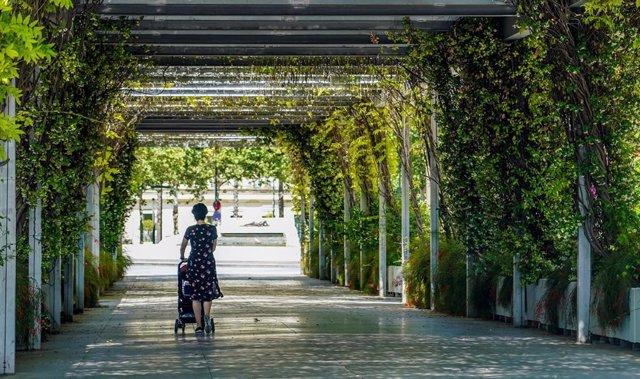 Una madre pasea con su carrito de bebe por los jardines del Cristina, un día antes de poder salir a practicar deporte y pasear por las calles y parques de Sevilla a 1 de mayo del 2020
